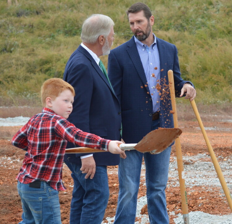 State Rep. Dan Douglas (center) talks with Scott Bennett, the director of the Arkansas Department of Transportation, after a groundbreaking ceremony today to celebrate the start of construction on new sections of the Bella Vista Bypass. Gavin Bose, Douglas's 7-year-old grandson, did his part to keep the highway project on schedule.