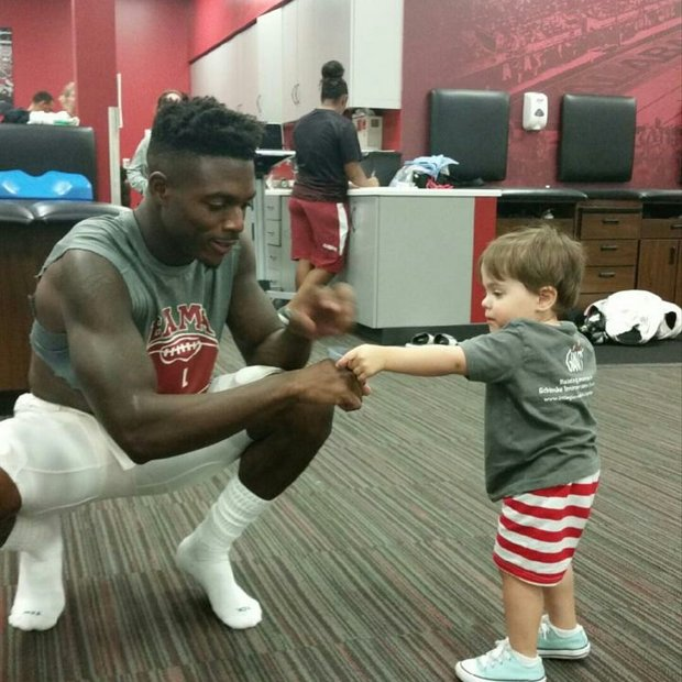 Kruz Davenport, 3, meets a Crimson Tide football player as he and his family work to spread awareness of his life-threatening genetic disorder, a rare form of dwarfism.