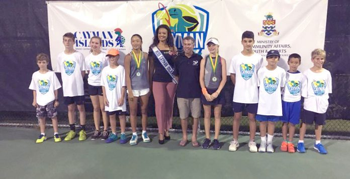 Cayman Cup ball kids stand with, fourth from left, girls runner up Madison Sieg, Miss Cayman Anika Conolly, Cayman Islands Tennis Club coach, and girls winner Catherine Aulia.