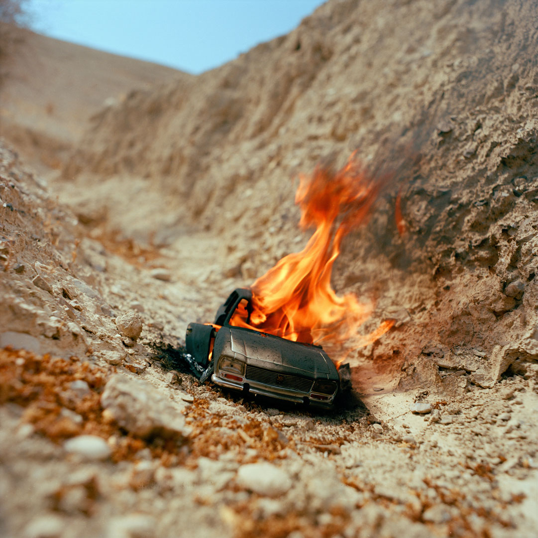"""""""The Burning Car (miniature)"""" , 2013 Archival pigment print, 16""""x20""""  Courtesy Yoav Friedlander & Carrie Able Gallery"""