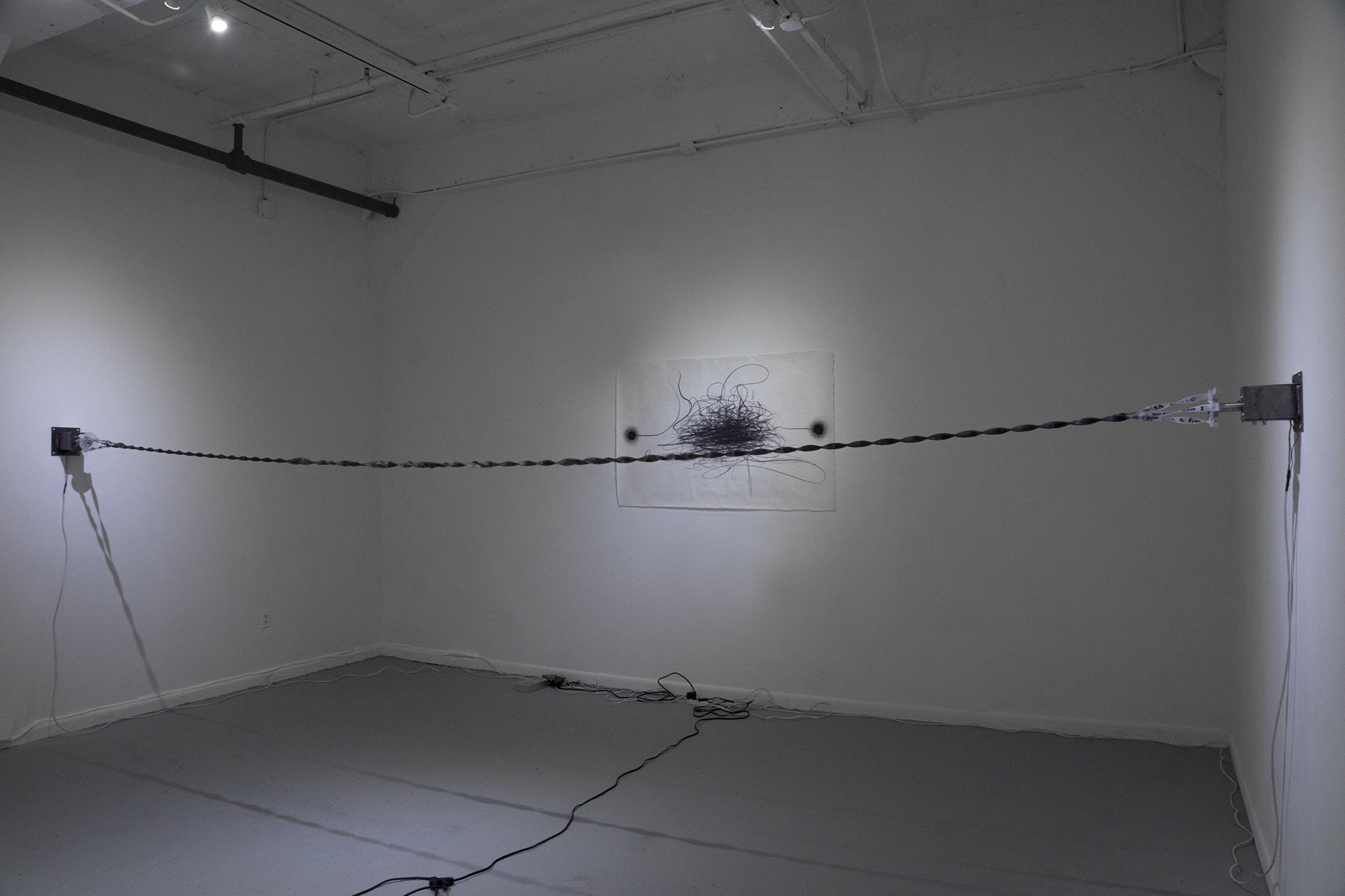 """  Entangled Descriptions  "" , 2017  Stepper motors, texts painted with dark gray plaster on three translucent silicone rubber bands, Arduino (programming board), Dimensions variable  Courtesy Hyunjung Rhee & Carrie Able Gallery"