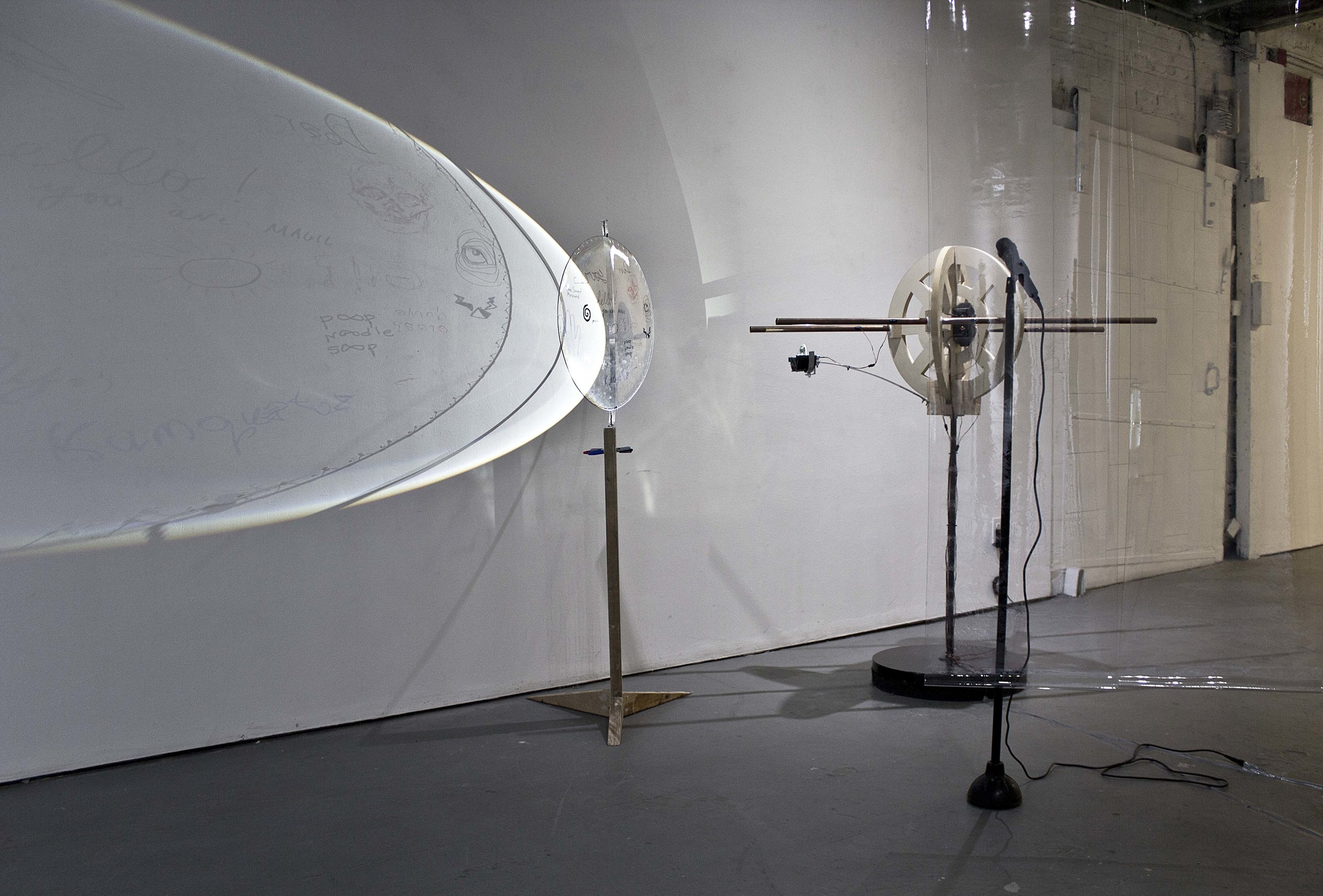 """Rotating Sketch Board & Sincerely Commo"" , 2017-2018  Copper pipe, LED, television lens, plunger, wood 2' x 5' x 2'/ 4' x 5' x 2'  Courtesy Kyungjin Kim & Carrie Able Gallery"