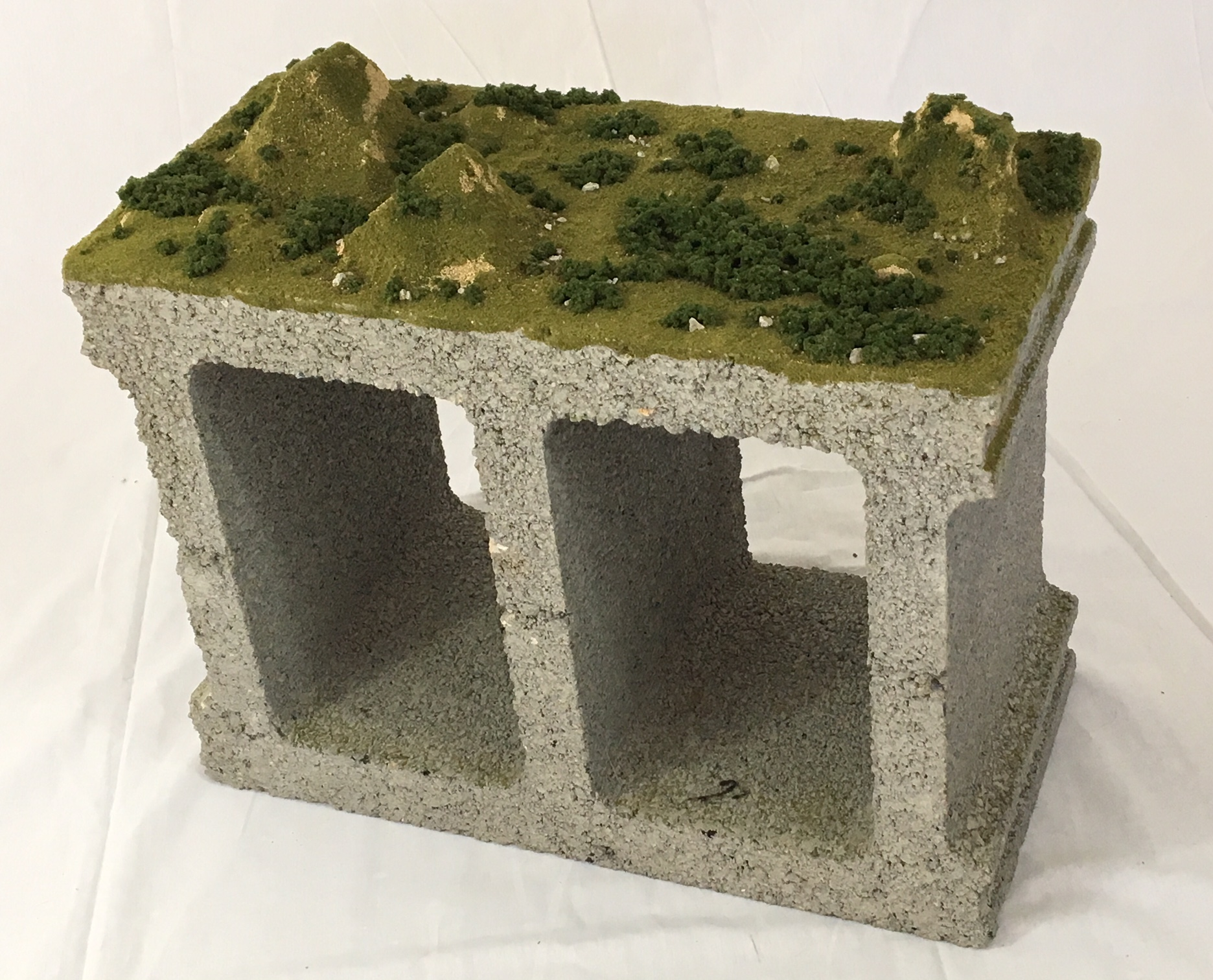 """Cinderscape"" , 2017  Cinder block, model train landscape material, gel medium, 13""x19""x12""  Courtesy Travis Childers and Carrie Able Gallery"