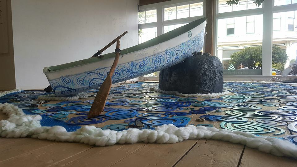 Aquatic inclinations of the disaster prone. - Installation with boat, repurposed campaign signs, Styrofoam blocks, cotton rope, floor runner, reclaimed wooden oars –altered & stained, paint, wood, string, pulleys, handle, reclaimed USCG anchor, twist ties, wax, varnish, string, caulk, sea shells.2019. Photograph by Violet Yashimiro.