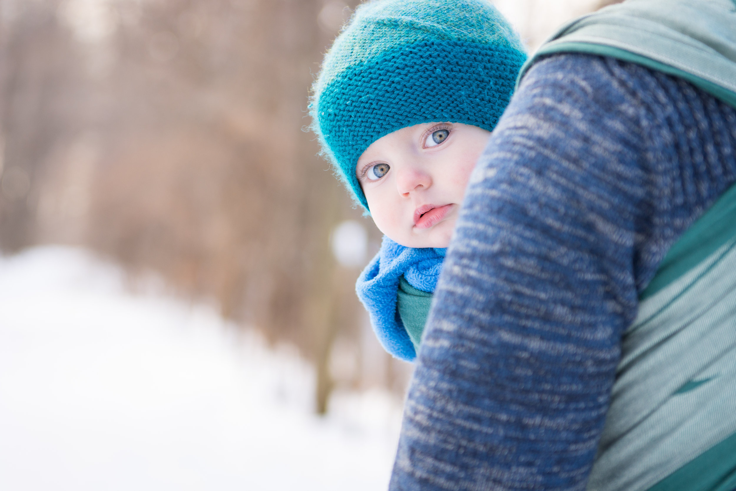 Little baby blues peeking out while babywearing with Dad in Ottawa Park.