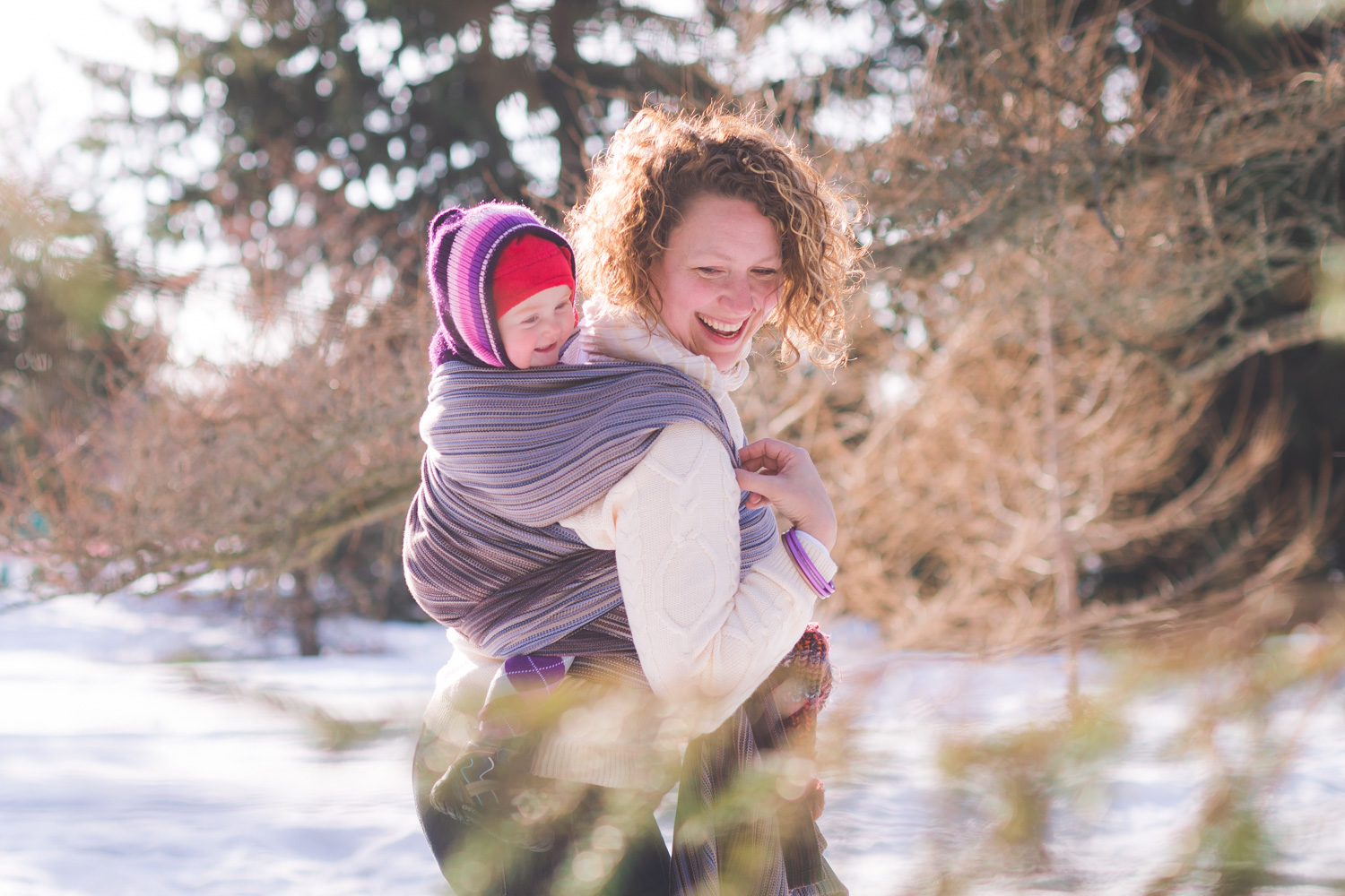 Mom and baby smiling and laughing babywearing in Ottawa Arboretum in the winter.