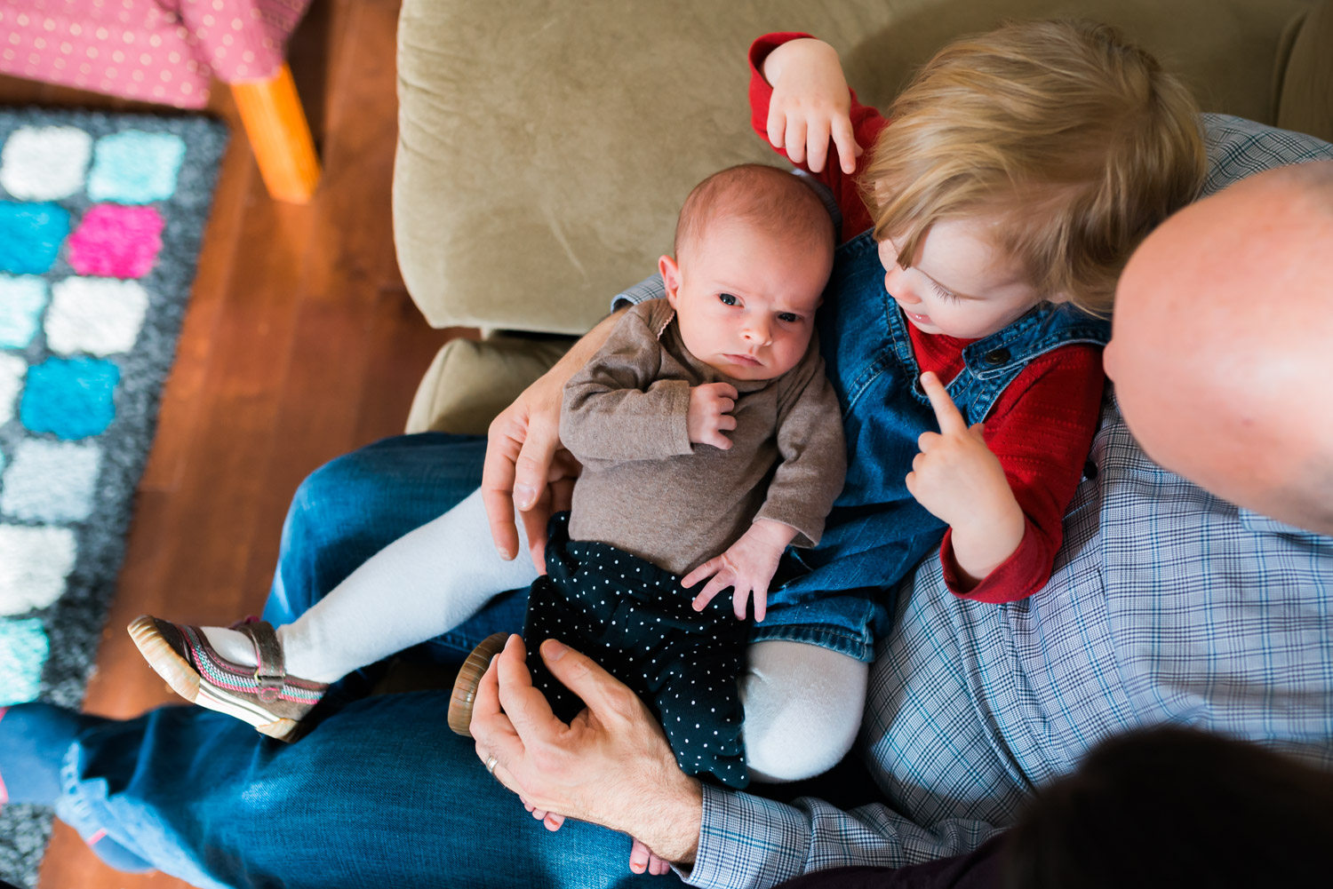 Big sister with newborn baby sister on couch during lifestyle session