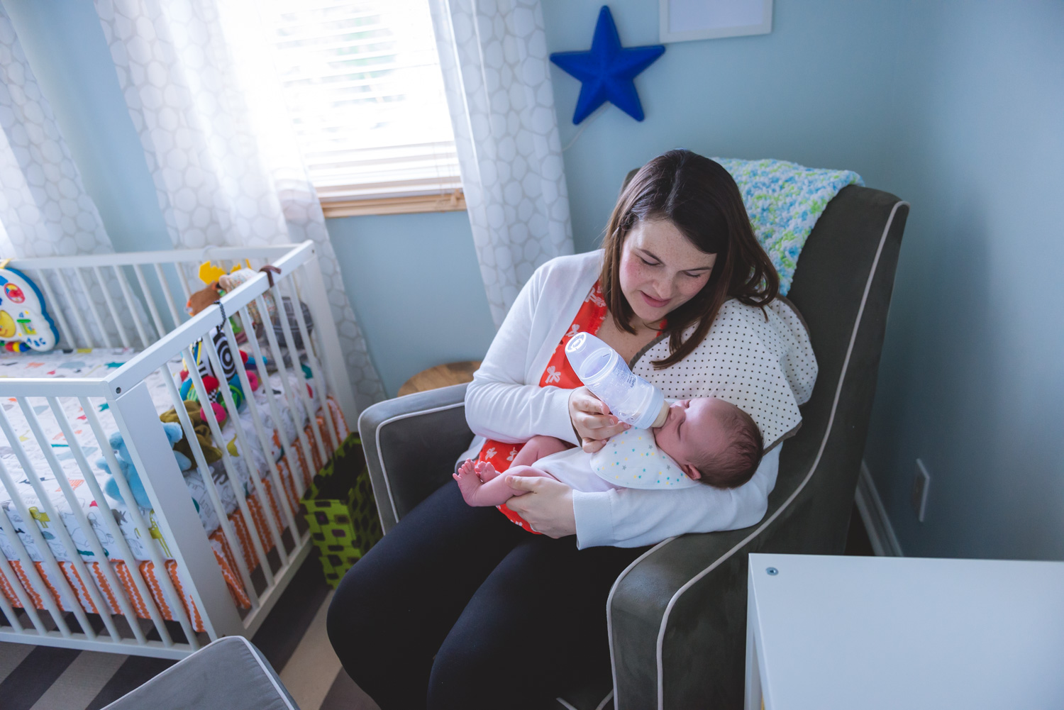 Mom bottle feeding her newborn son in rocking chair at home