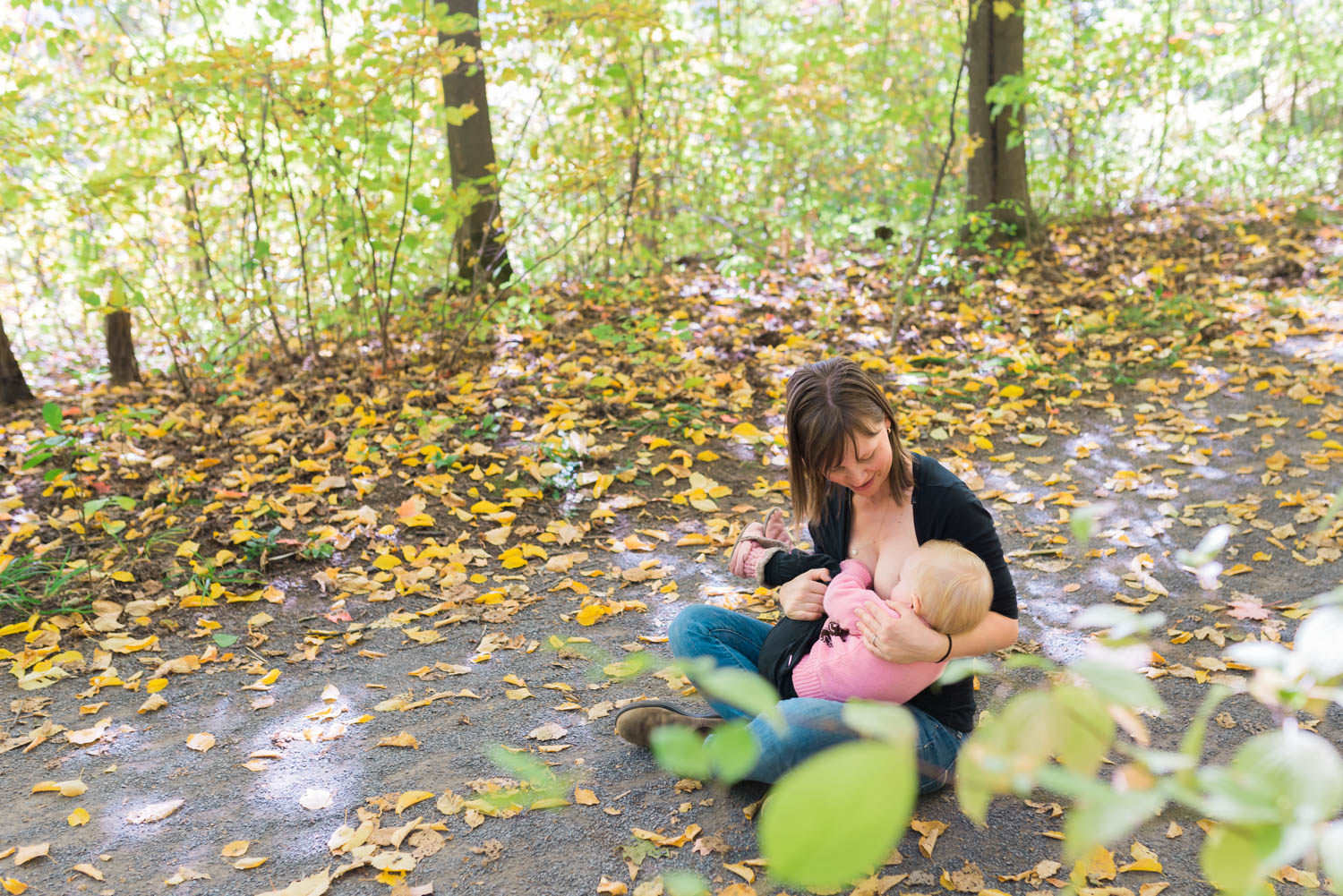 Mom breastfeeding daughter in the fall at Mer Bleu outdoor session