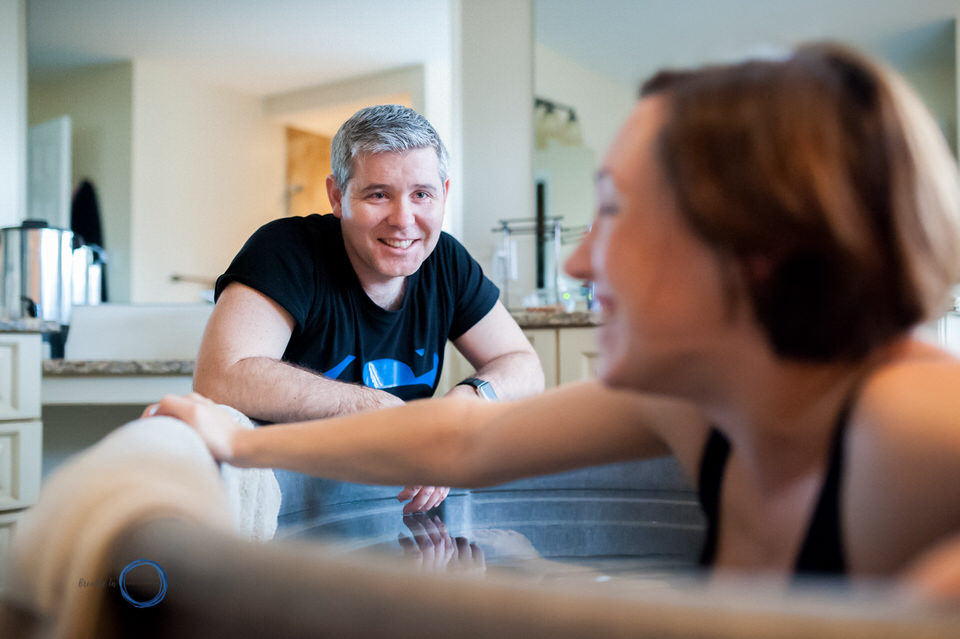Man looks at his beautiful partner lovingly while she is in labour.