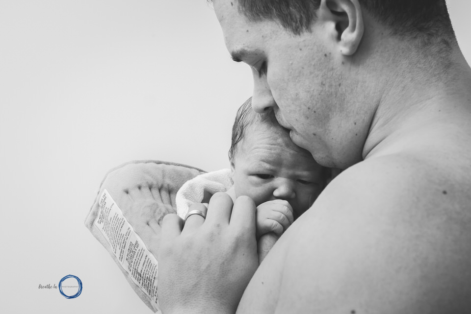 Dad holds infant skin on skin after home birth with Ottawa Midwives.
