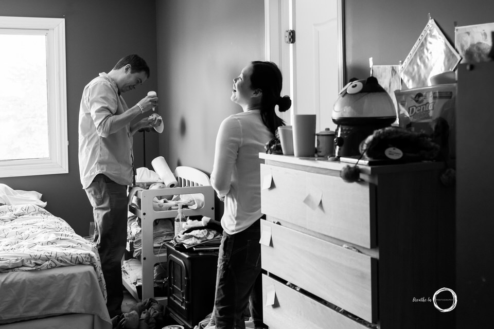 Mom laughing Dad changing baby's diaper during in home lifestyle baby photos in Ottawa.
