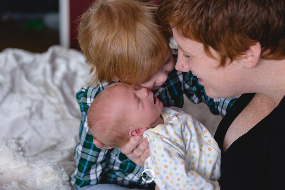 Big brother with red hair and plaid shirt cuddles with his new baby brother and mom smiles while holding newborn.