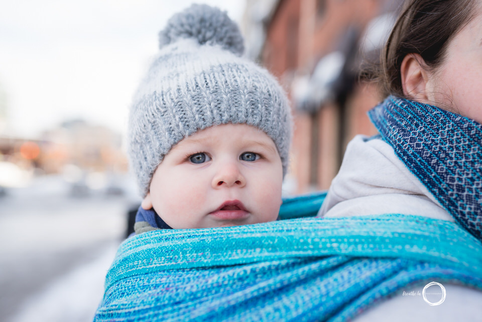 Baby boy with grey hat looking at camera with blue eyes.