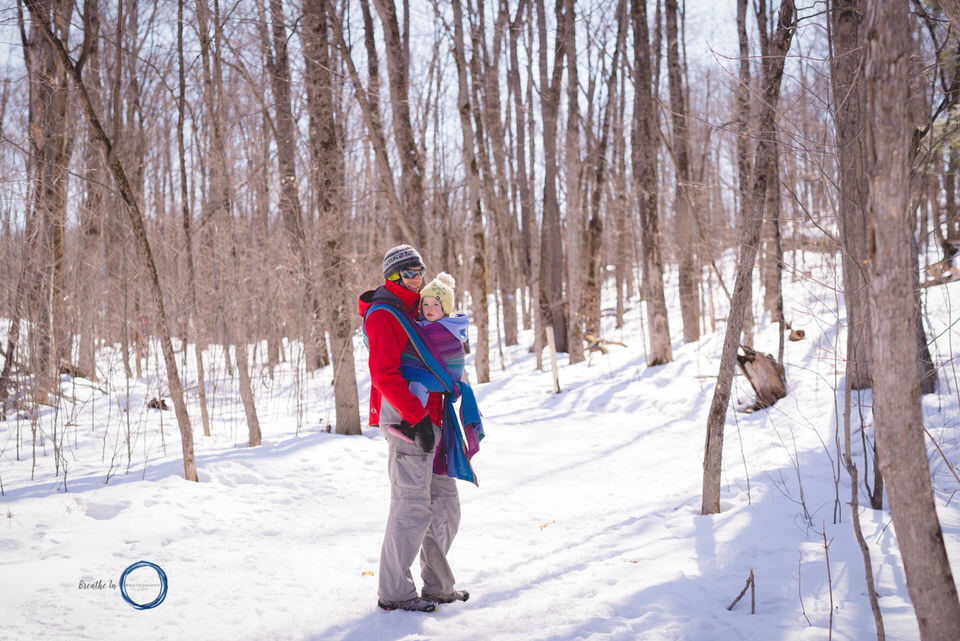 Dad carrying his toddler in handwoven wrap on a very cold day in Gatineau Park.