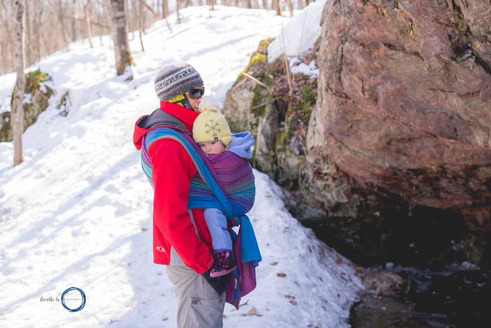 Daughter cuddles with dad babywearing on hike.