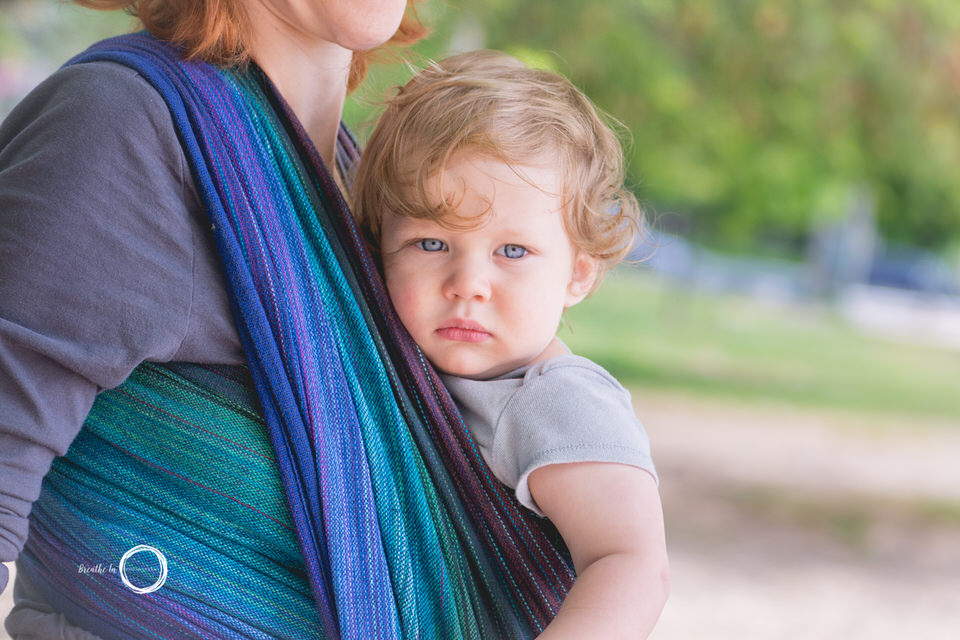 Toddler looking at camera in beautiful handwoven wrap carried by Mom on beach.
