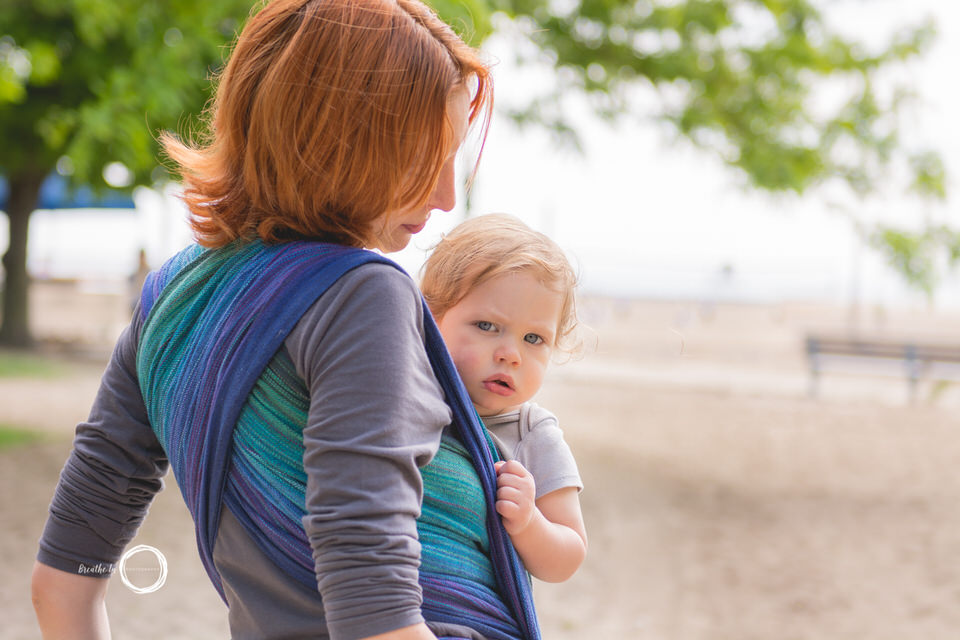 Toddler peeking over Mom while being carried in handwoven wrap on beach.