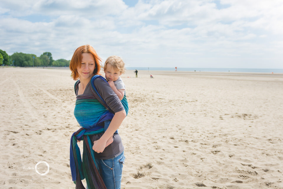 Mom carrying son on her back in handwoven on beach during babywearing photos.