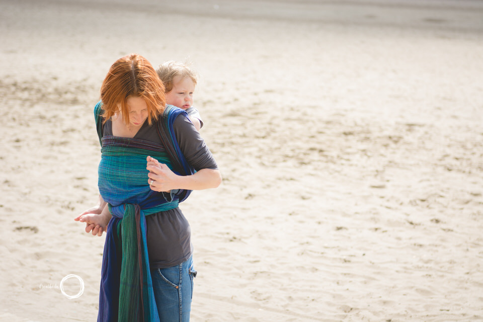 Cuddling with toes during babywearing photo session on beach.