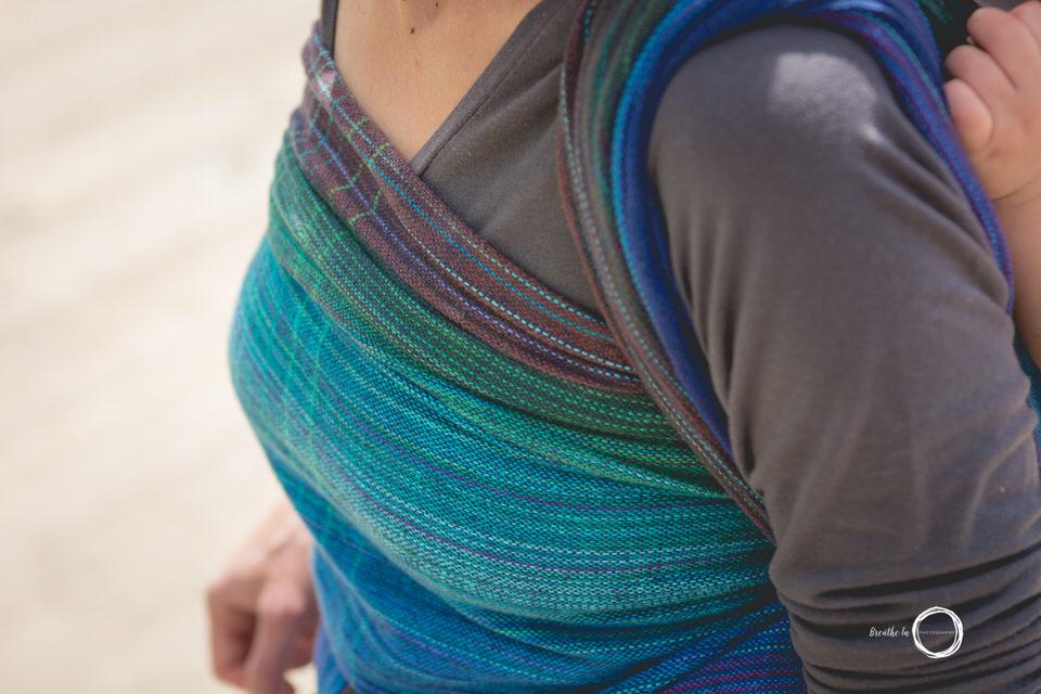 Details of beautiful handwoven babywearing wrap on beach.