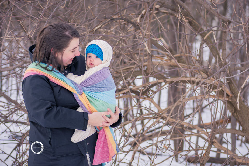 Mom carrying baby boy in Girasol Rainbow Wrap in the snow near Vanier Library.
