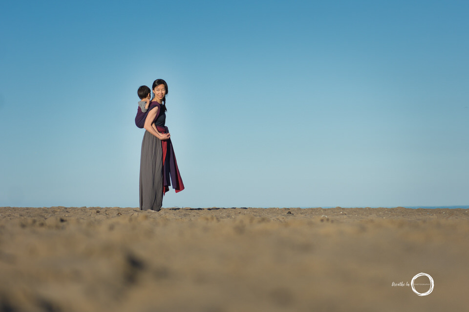 Babywearing photography on beach in ETLA wrap with toddler on mom's back walking in the sand.