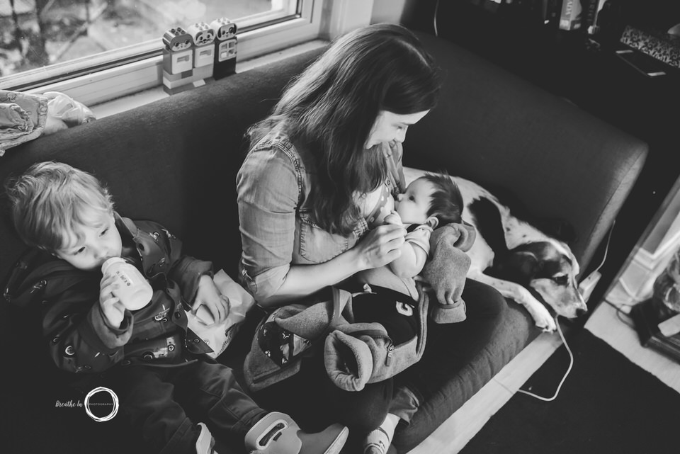Real life family moments during in home newborn photo session.  Baby breastfeeding and toddler drinking from bottle on couch with mom.