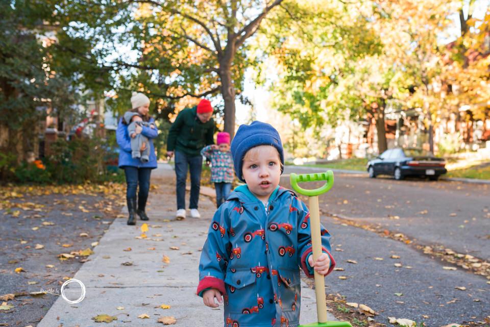Toddler holding play shovel during family photo shoot.