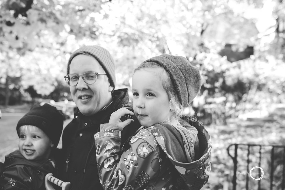 Dad holding daughter and son smiling.