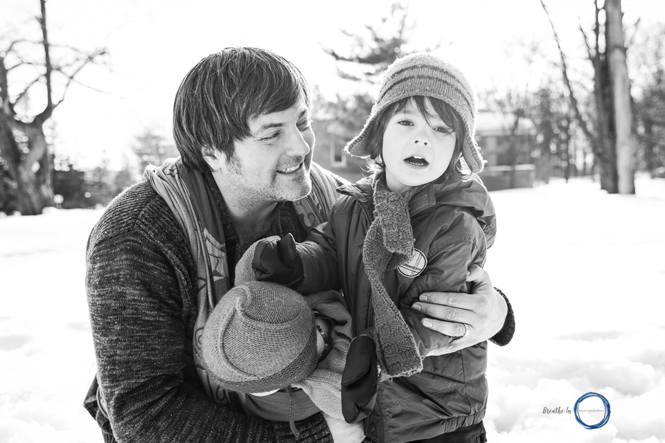 Dad hugging his sons during babywearing photo session in Vanier.