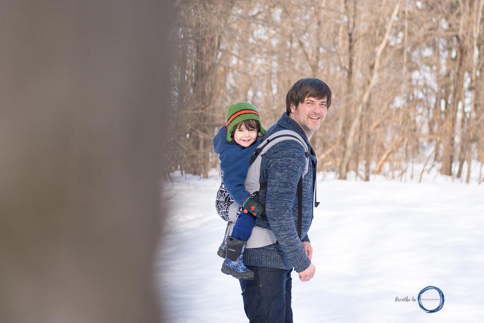 Dad carrying toddler son in Tula at Vanier Sugar Bush in Ottawa.