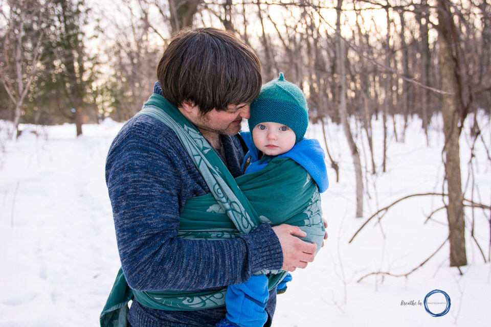 Dad snuggling his son in woven wrap during babywearing photography fundraiser in winter.