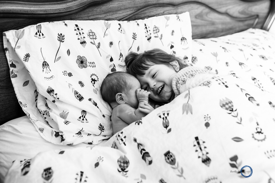Big sister and her newborn brother play in bed during in home lifestyle session in Ottawa.