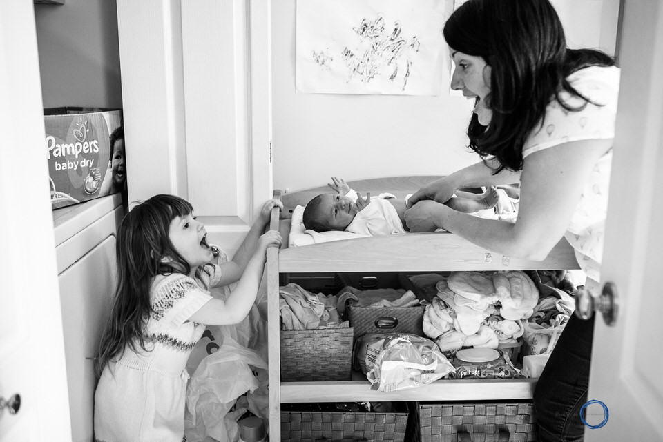 Mom and big sister talking while changing newborn's diaper during photo session in Ottawa.