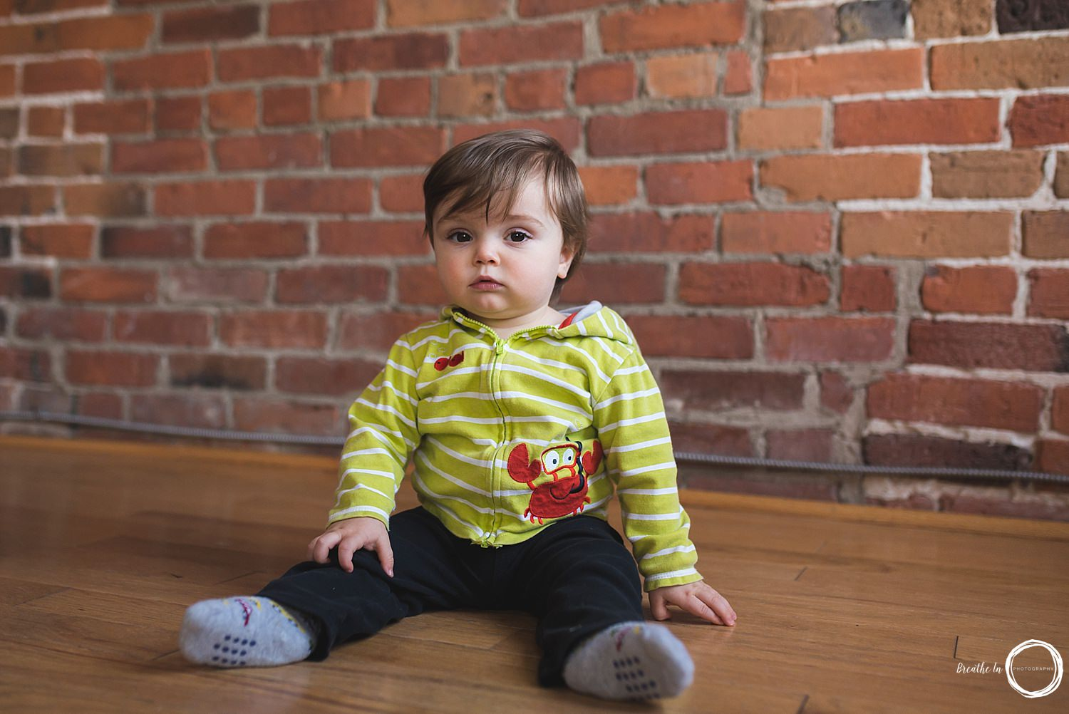 Baby boy looking right at camera in green sweatshirt in front of brick wall in Byward Market.
