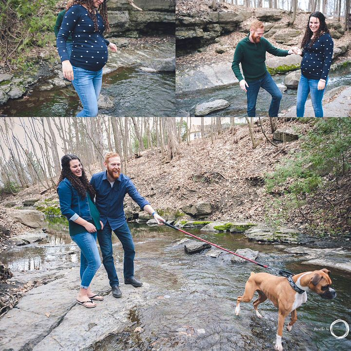 Pregnant Mom in blue and white sweater, Dad in jeans by the water with their dog laughing and smiling.