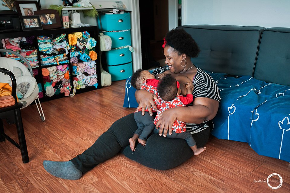 Smiling woman breastfeeding her twin daughters at home in Ottawa during photo session.