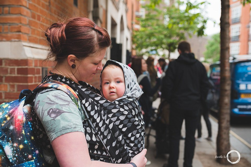 Mom and baby in Woven Wings wrap waiting to get into the Wrap Show in London, UK.