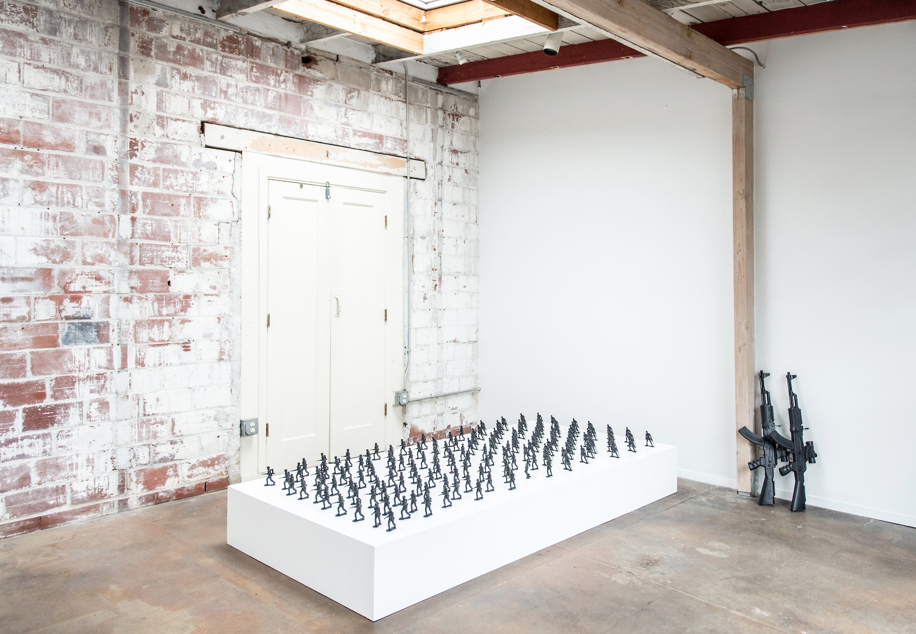 "Installation View. Wooden platform, toy soldiers (4""), toy AK-47 assault rifle (2½ ft), aerosol paint."