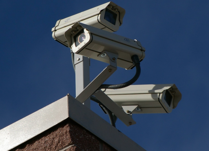 A cluster of security cameras on the corner of an unidentified building. Via  Wikimedia .