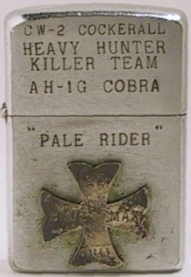 "1960 Zippo that belonged to Chief Warrant Office (CW-2) Cockerall. Hunter Killer Teams in Vietnam consisted of AH-1G Cobra and one OH-6A Helicopter working together. It also reads ""Pale Rider"" and has an attached cross that reads ""Blue Max - 25 Kills""."