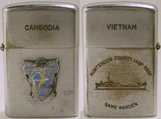 "Vulcan brand lighter marked ""Cambodia"" and an attached badge for USS Hunterdon  County Game Warden.  The back reads""Vietnam - AGP 838 USS Hunterdon County  Game Warden"" and has a line drawing of the ship"