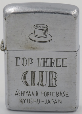 """1946-49 Zippo which has been engraved with the image of a top hat and """"Top Three Club - . Top Three Club Ashiya Air Force Base, Kyushu Japan"""" during the US occupation of Japan."""