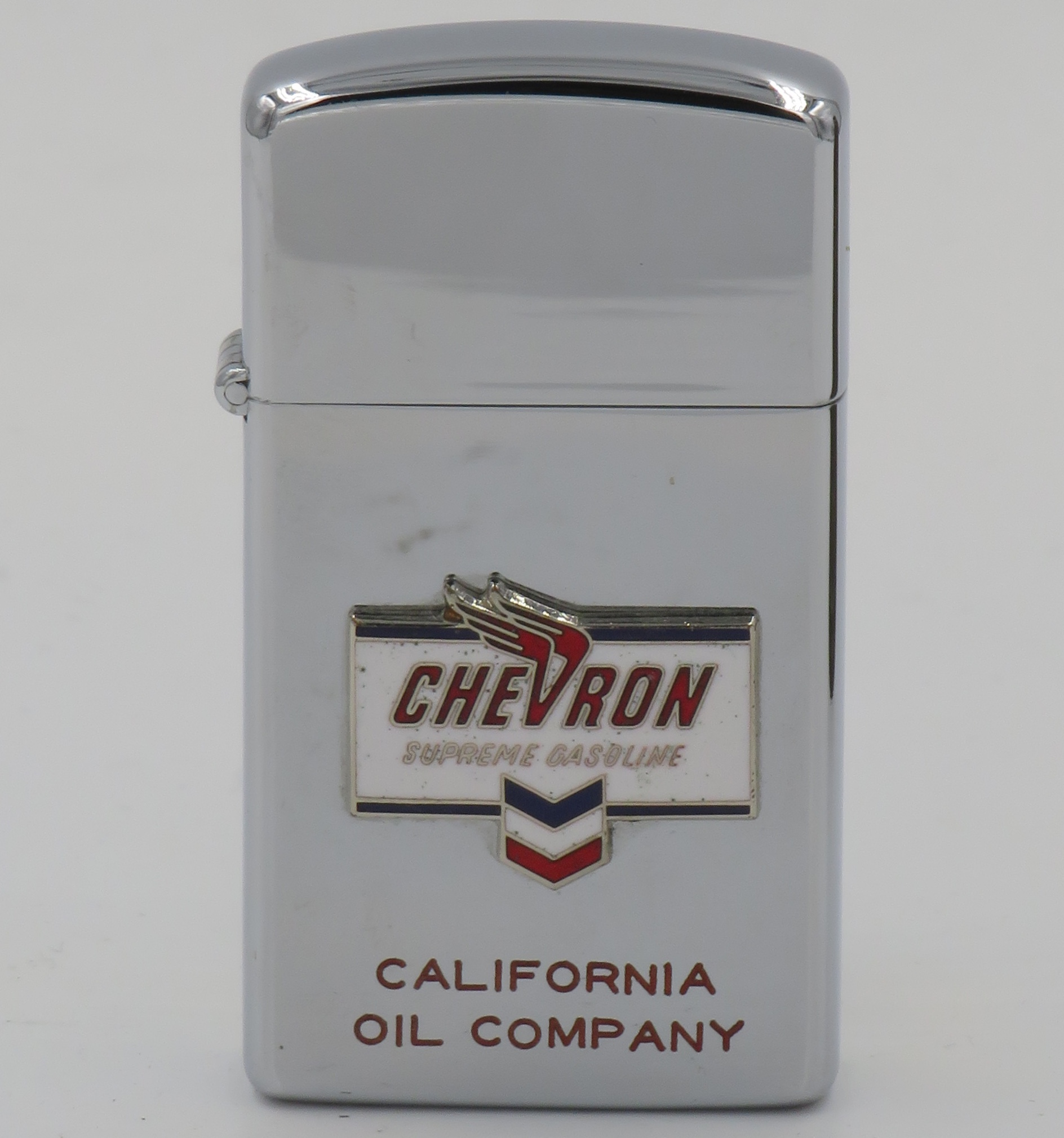 """Chevron slim 1961 slim Zippo with Chevron Supreme Gasoline attached badge and """"California Oil Company"""" engraved"""