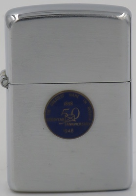 """1948 Goodyear Zippo with attached emblem. The emblem reads """"Goodyear 50th Anniversary The Greatest Name in Rubber"""". Goodyear was founded in 1898 and was named after Charles Goodyear, the discoverer of rubber vulcanization"""