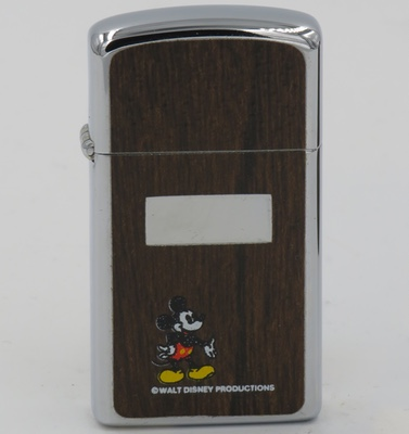 This slim 1976 Zippo bears the image of Mickey on a vinyl appliques simulating wood grain