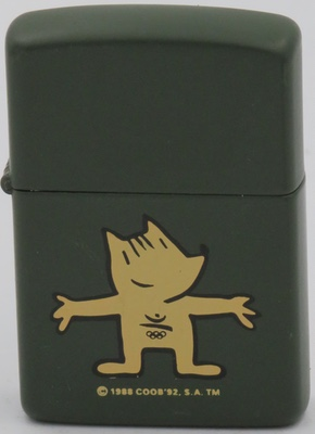 1987 prototype Zippo with Cobi,  the official mascot of the 1992 Summer Olympics in Barcelona, Spain. He is a Catalan Sheepdog in Cubist style inspired by the interpretations of Picasso of a masterpiece from Velázquez, Las Meninas