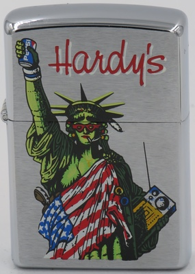 "1997 Zippo with a smoking Statue of Liberty in sun glasses wrapped in the Stars and Stripes, packing a boom box and a gun, raising a beer on high, for ""Hardy's"""