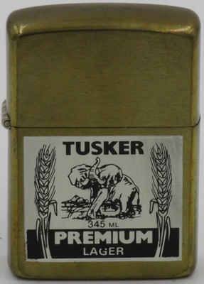 1997 brass Zippo with a prototype design for Tusker Premium Lager which is produced in Nairobi, Kenya. The brand was first marketed in 1923, shortly after the founder of Kenya Breweries Ltd, George Hurst, was killed by an elephant during a hunting accident